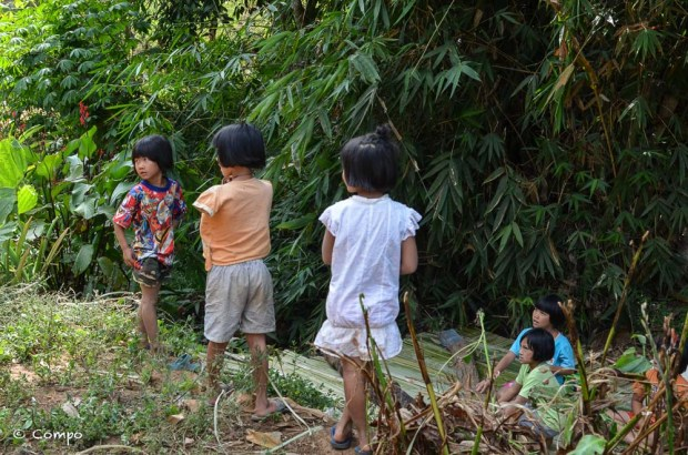 Tourist paprazzi interrupt children from a hill tribe whilst playing in a ditch in northern Thailand.